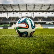 A football on the pitch in a stadium